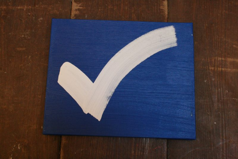 A white checkmark on a blue wooden panel
